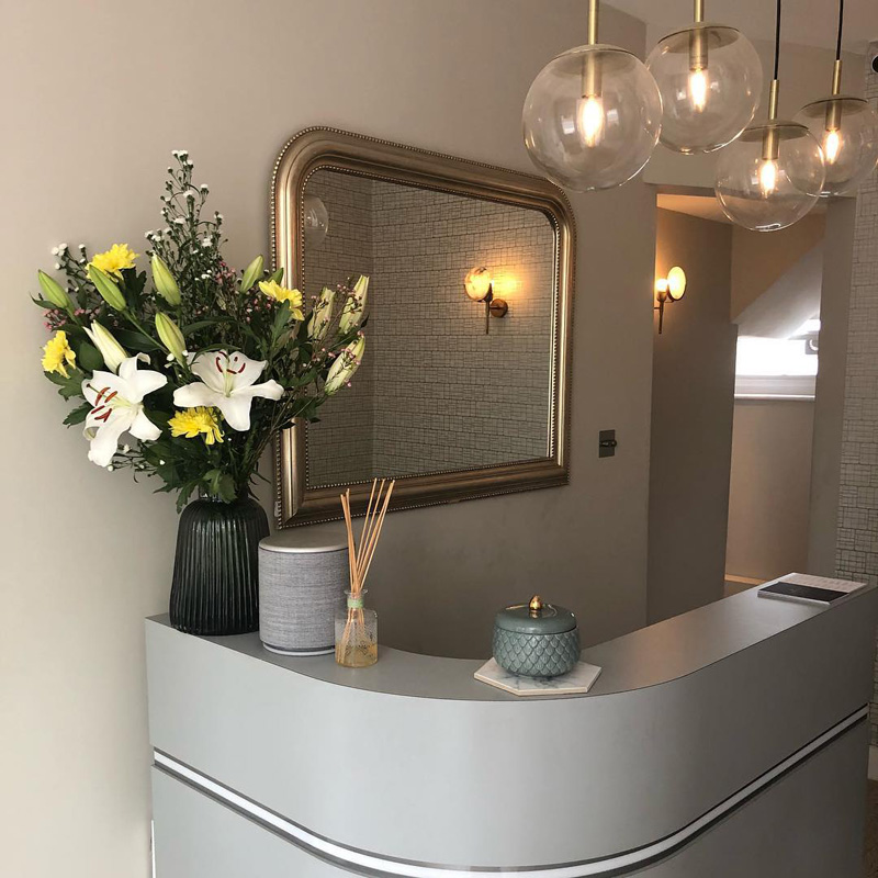 salon reception desk in grey with gold mirror and flower vase on top