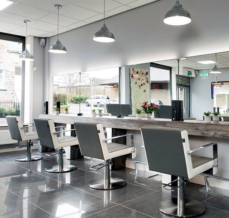 grey and white salon chairs in a hairdressers room