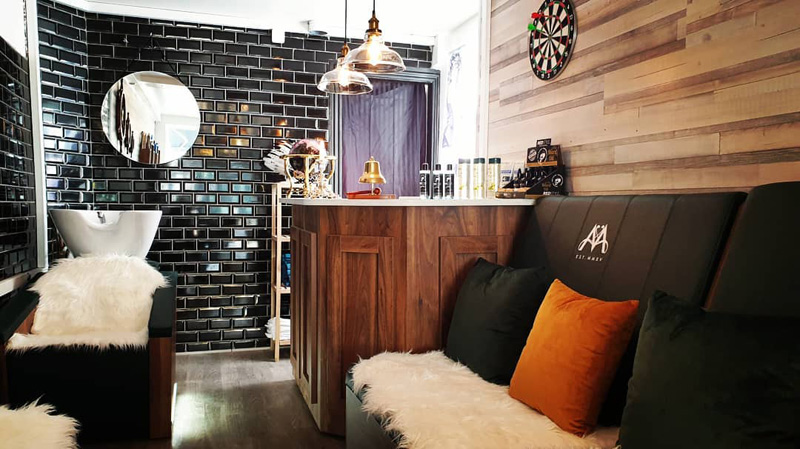 cozy rustic barbers shop with black tiles and faux fur covers