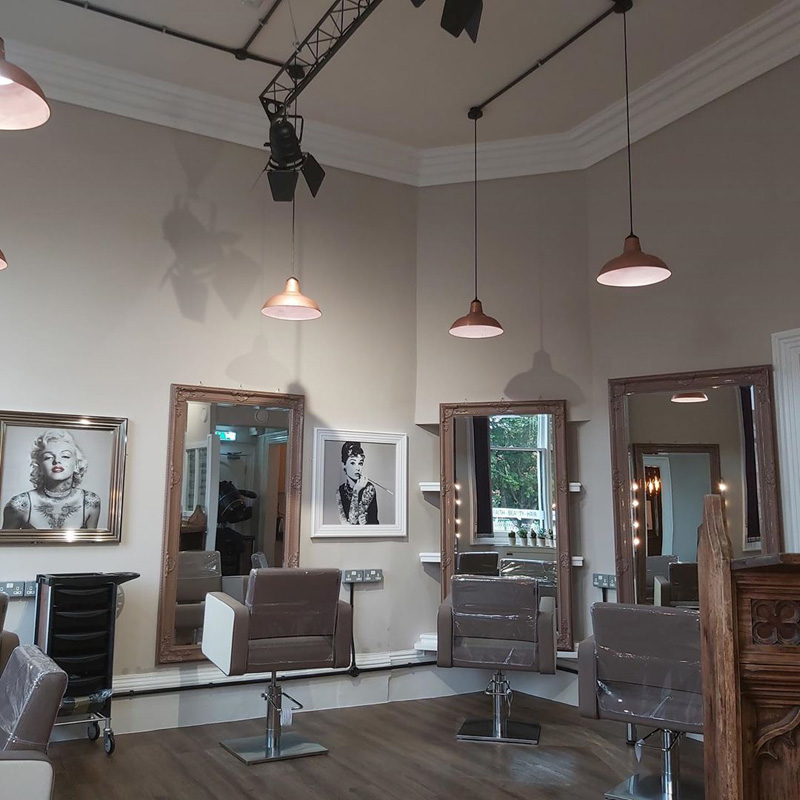hair salon interior with wall art and copper lamps