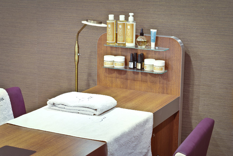 brown manicure table with towel and nail polish display
