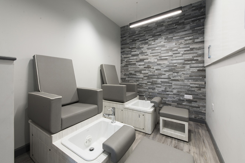 grey and white pedicure chairs with feet basin stone wall