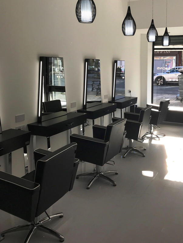 hair salon with styling mirror and chairs